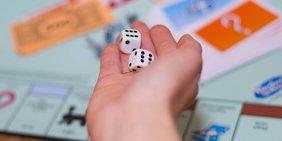 Mensch spielt Monopoly und hat die Würfel in der Hand