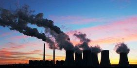 Kraftwerk mit dampfenden Kühltürmen vor Sonnenuntergang