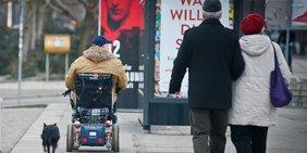 Mann fährt mit seinem Rollstuhl und führt dabei seinem Hund spazieren, im Hintergrund geht ein älteres Paar spazieren
