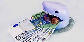 Plastikfigur eines Hais beißt in Geldscheine und Münzen