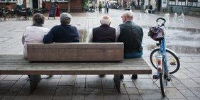 Rentner auf Bank mit Fahrrad