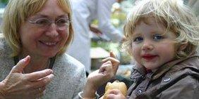 Frau mit Kind das ein Brötchen isst und in die Kamera schaut