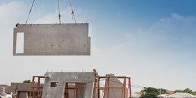 Hauswand eines Fertigteilhaus wird von einem Baukran angehoben