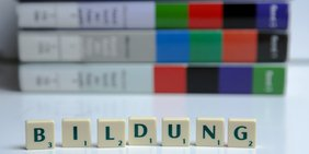 """Scrabble-Buchstaben """"Weiterbildung"""" vor Büchern aufgestellt"""