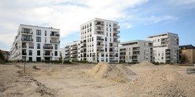 Mehrgeschossige Neubauten hinter einem Bauplatz